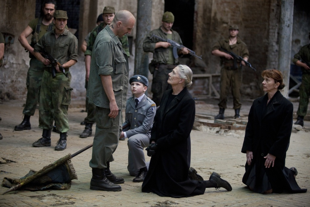 (Centre Group) Young Martius (Harry Fenn) and Volumnia (Vanessa Redgrave) kneel before Coriolanus (Ralph Fiennes) to plead the case of Rome.